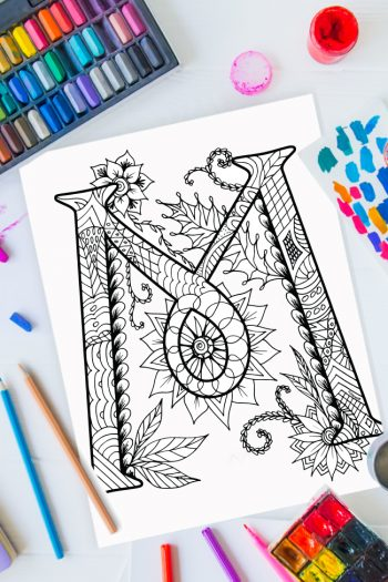 Zentangle alphabet coloring pages - letter m zentangle design on background of paint, colored pencils and art supplies