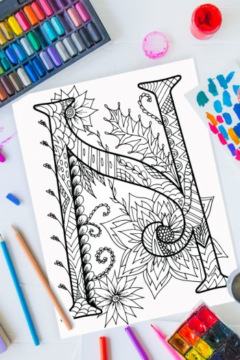 Zentangle alphabet coloring pages - letter n zentangle design on background of paint, colored pencils and art supplies