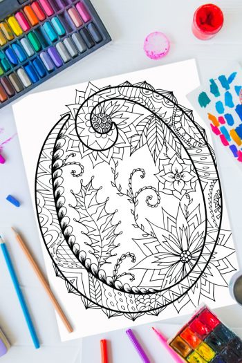 Zentangle alphabet coloring pages - letter o zentangle design on background of paint, colored pencils and art supplies