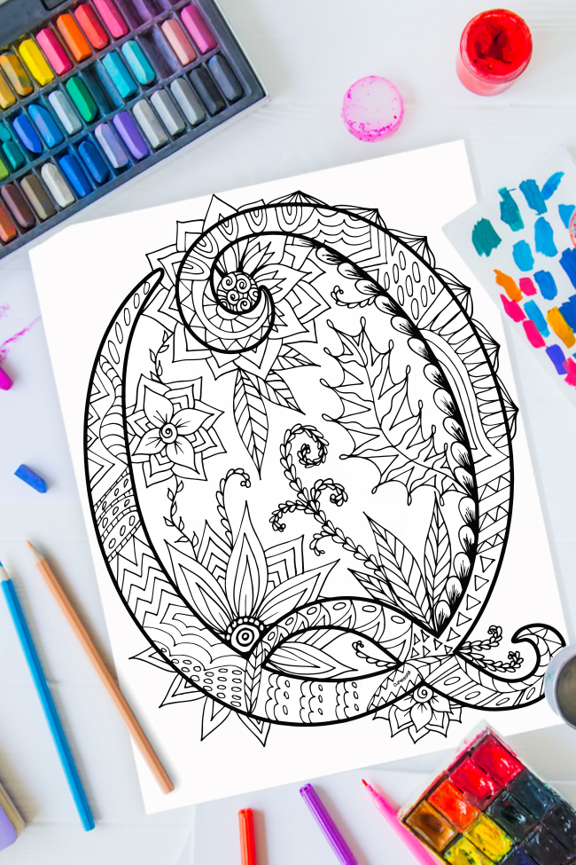 Zentangle alphabet coloring pages - letter q zentangle design on background of paint, colored pencils and art supplies