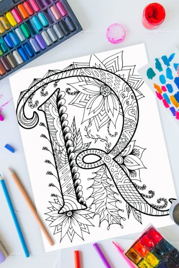 Zentangle alphabet coloring pages - letter r zentangle design on background of paint, colored pencils and art supplies