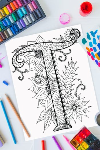 Zentangle alphabet coloring pages - letter t zentangle design on background of paint, colored pencils and art supplies