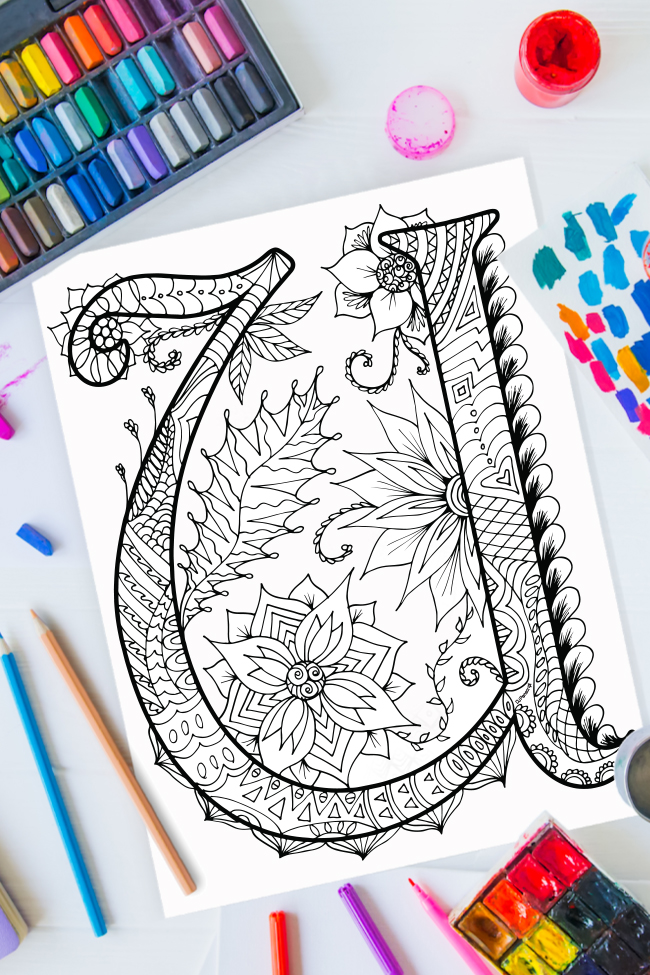 Zentangle alphabet coloring pages - letter u zentangle design on background of paint, colored pencils and art supplies