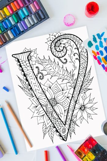 Zentangle alphabet coloring pages - letter v zentangle design on background of paint, colored pencils and art supplies