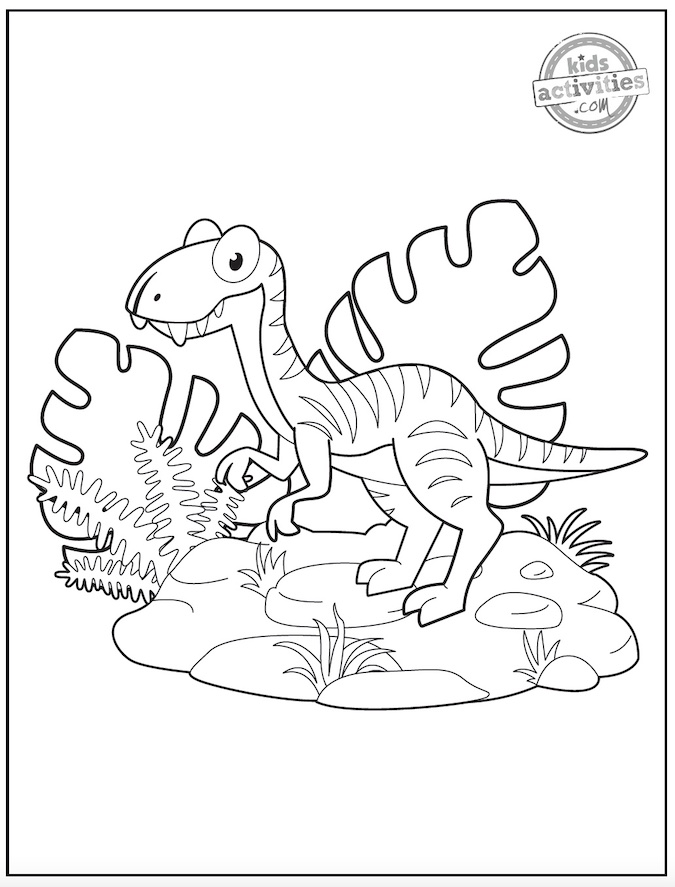 Black and white coloring page showing a cartoon style velociraptor surrounded by tropical leaves and rocks