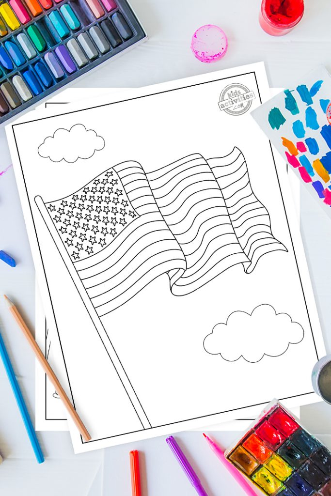 American flag coloring page on a desk with paint, pastels and art supplies