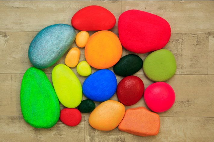 Painting Rocks ideas for kids and beginners - apply a base coat of paint before other decorations.  Shown are a collection of brightly colored painted rocks.