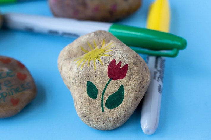 Flower painted on rock with Sharpie pens - shown is a red tulip painted on gray stone.
