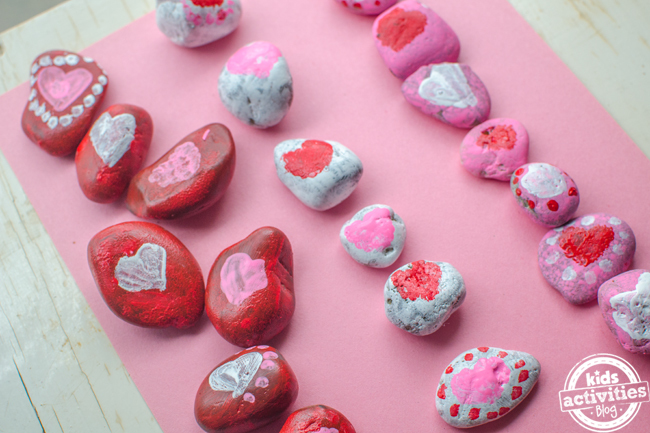 Red, pink and white painted stones with hearts and heart decorations added painted by kids.