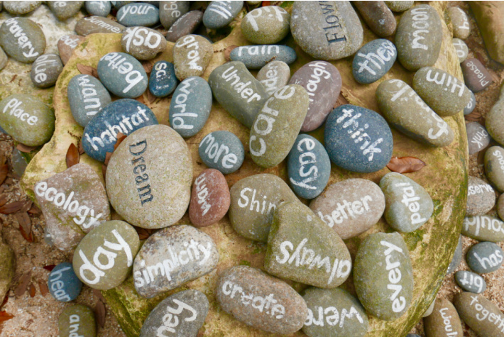Words painted on rocks like dream, ecology, day, always, shine, think, moon, flower, better