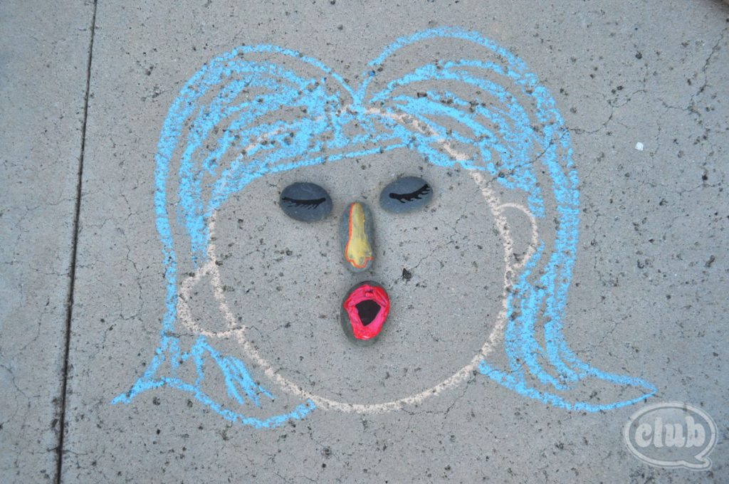 Painted rock eyes, nose and mouth shown in a chalk created face with hair.  It is so funny and cute from Club Chica Circle site.