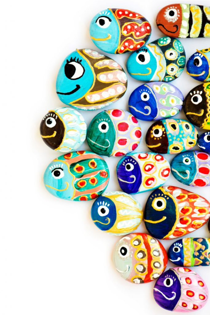Painted rocks make up a school of fish with each painted rock looking like a different type of fish with colorful decorations.