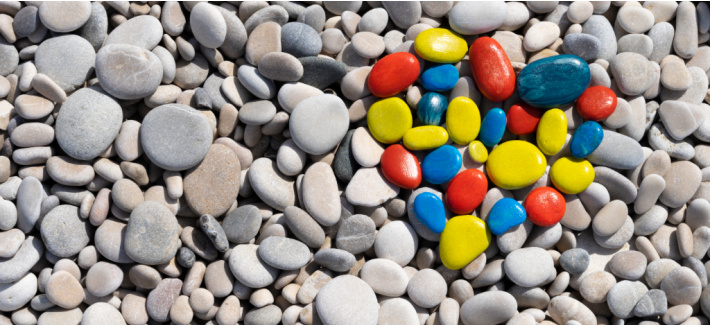 Single color painted rocks: red, orange, yellow blue and light blue arranged on grey stones into the shape of a heart.