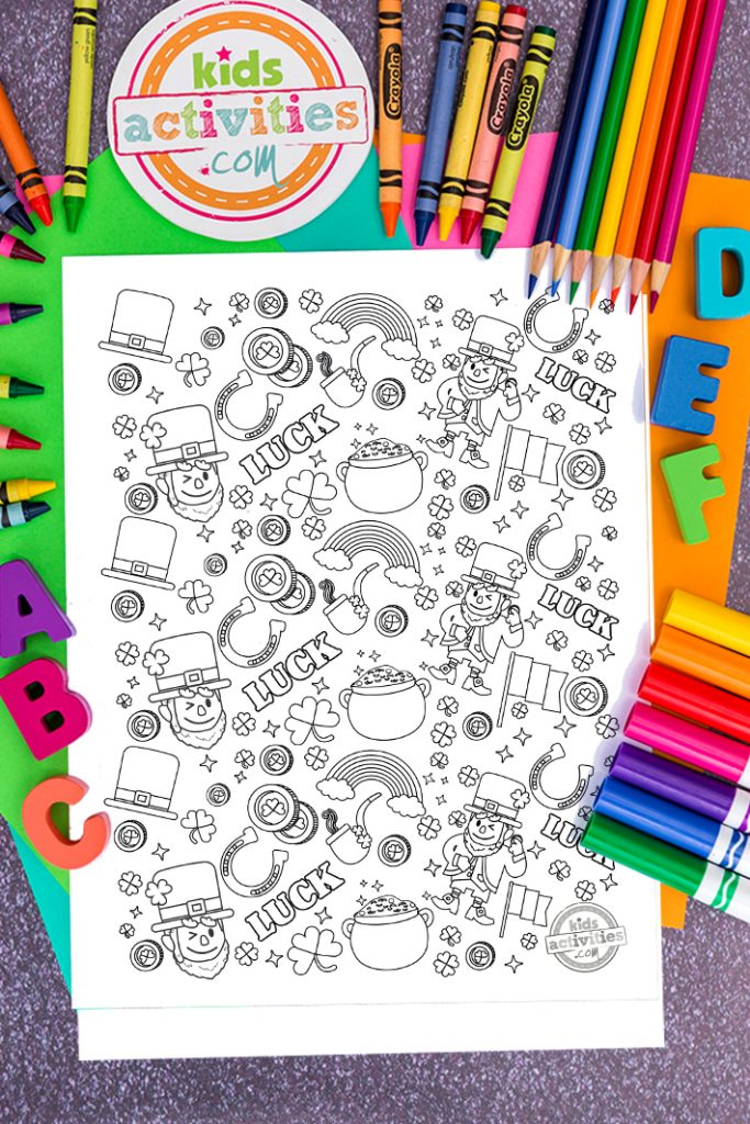 Coloring page of St Patrick's Day doodles with leprechaun, rainbow, shamrocks, gold coins, Ireland's flag on a desk with colored paper, pencils, crayons, markers and ABC's
