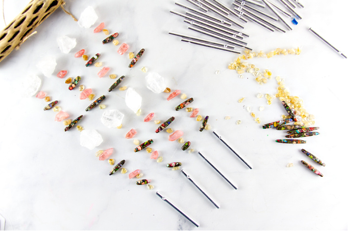 assorted beads and metal chimes laid out to make wind chimes