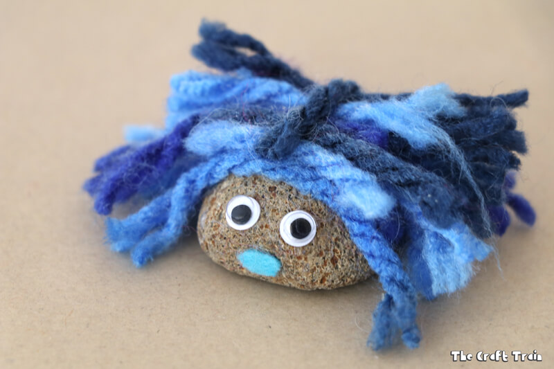 Fluffy painted pet rock with yarn hair from The Craft Train - one rock with googly eyes and blue yarn hair pictured