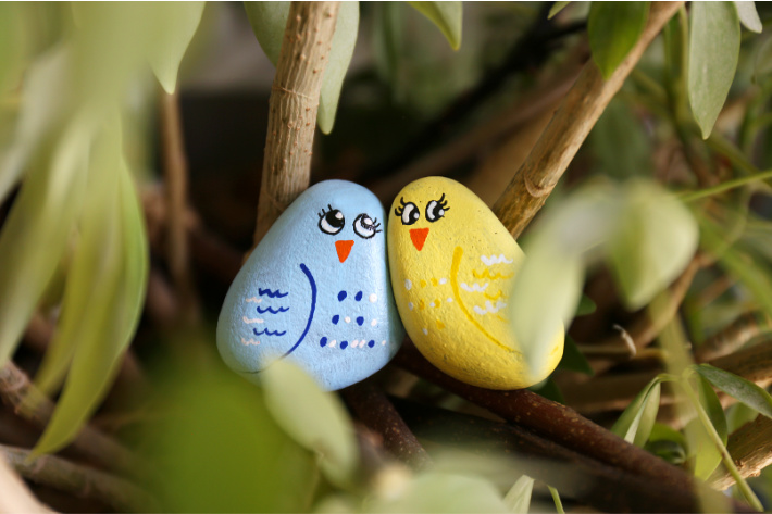 love bird painted rocks sitting in a tree - one bird is a blue painted rock and the other is yellow painted rock