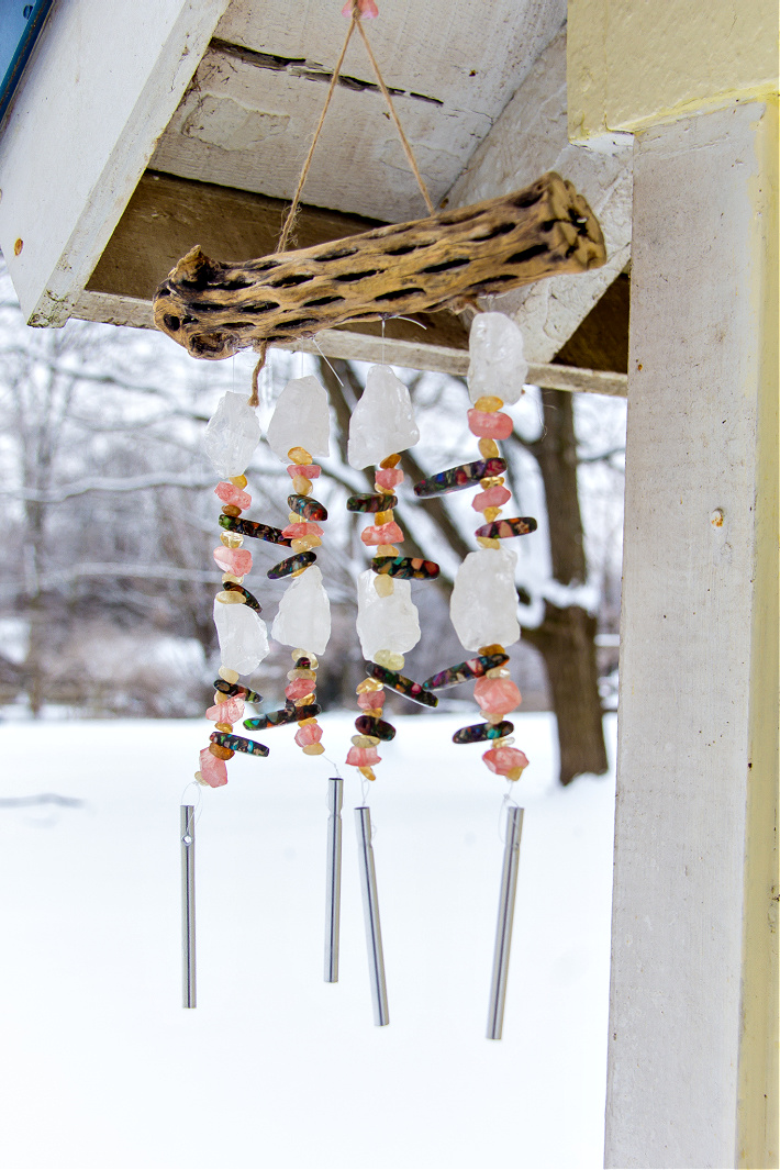 handmade beaded wind chimes on cholla wood hanging from a garden shed