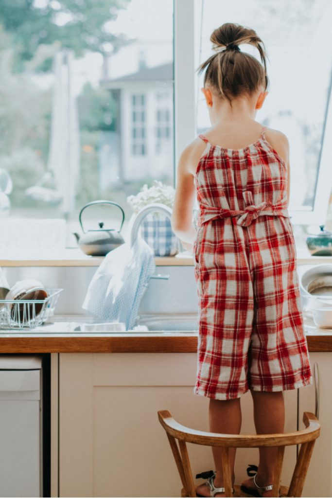 Getting kids to do chores willingly without complaining - girl standing on chair at sink washing dishes