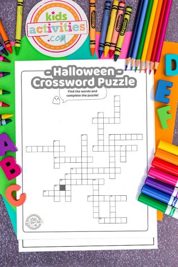 Halloween crossword puzzle sheet on top of brightly colored paper with crayons, coloring pencils, markers and magnetic ABC letters.