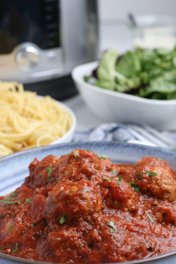 The Best Homemade Instant Pot Meatballs - A steaming platter of homemade sauce with Instant Pot meatballs, and spaghetti noodles and salad in the backround
