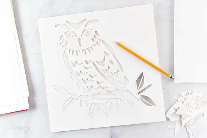 An owl stencil on top of a canvas to be traced to make a painting.