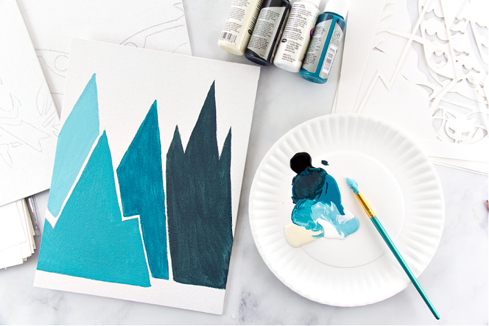Blue mountains being painted on a canvas with paint being mixed on a paper plate.