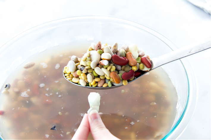 Dried beans soaking in water and then skins being removed