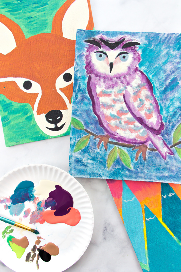 A fox, owl, and mountain paintings on canvas with acrylic paint for kids with a paper plate with paint on it.