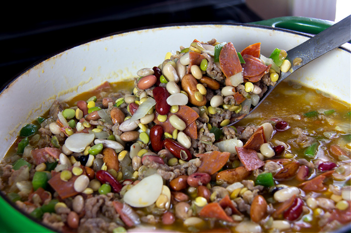 A green pot on the stove filled with beans, broth, pepperoni, and ground sausage.