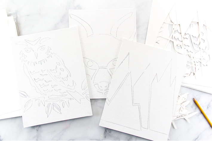 Mountains, an owl, and a fox traced from stencils onto canvas for kids to paint.