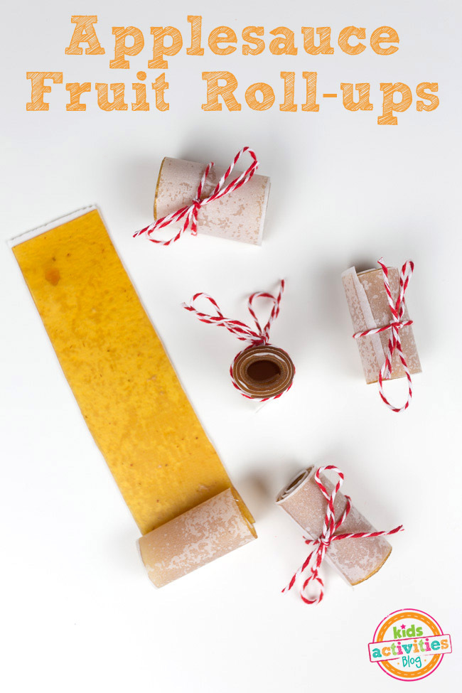 Homemade apple fruit leather snack or applesauce fruit roll ups shown on white counter in various stages of being rolled up