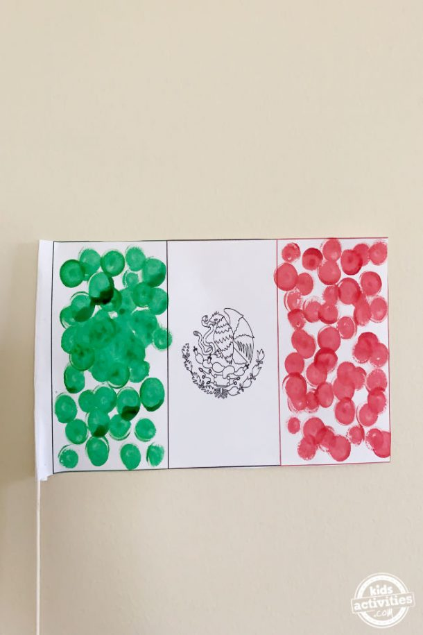Mexican flag made by preschool kids using dot markers with pole shown