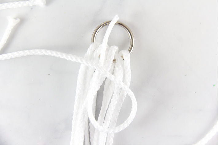Macrame cord wrapped over a metal ring with a loop for securing it.