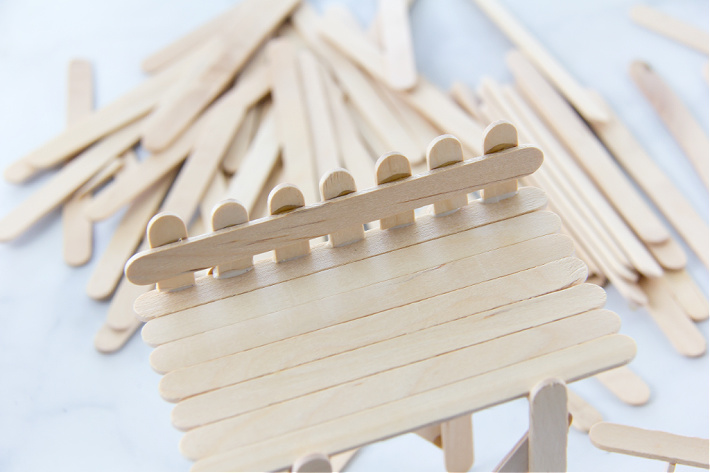 a popsicle stick fence being made on top of an observation deck