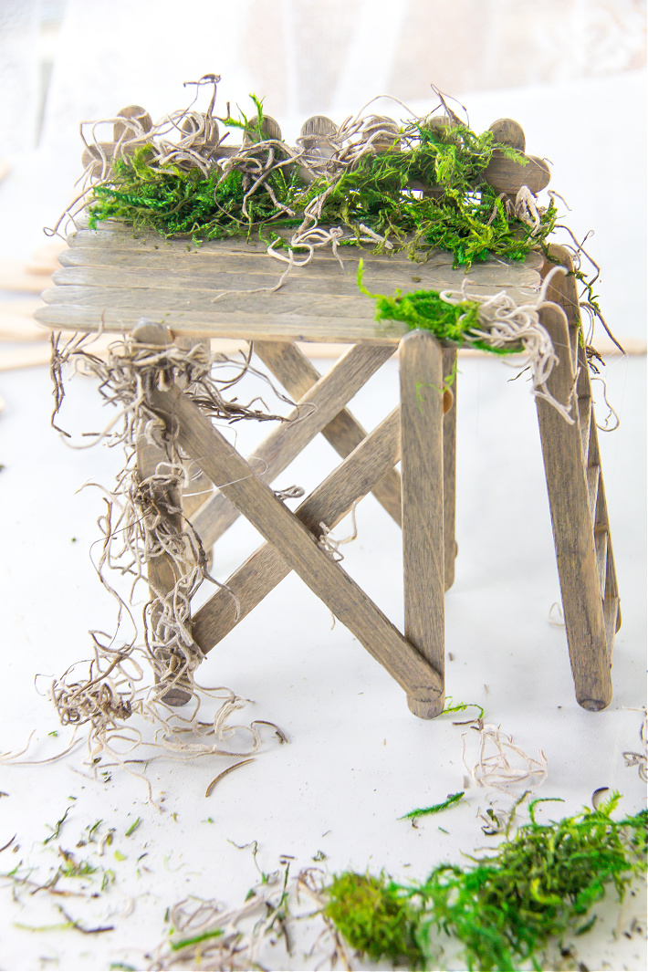 Moss attached to a handmade popsicle stick observation deck for a fairy garden.