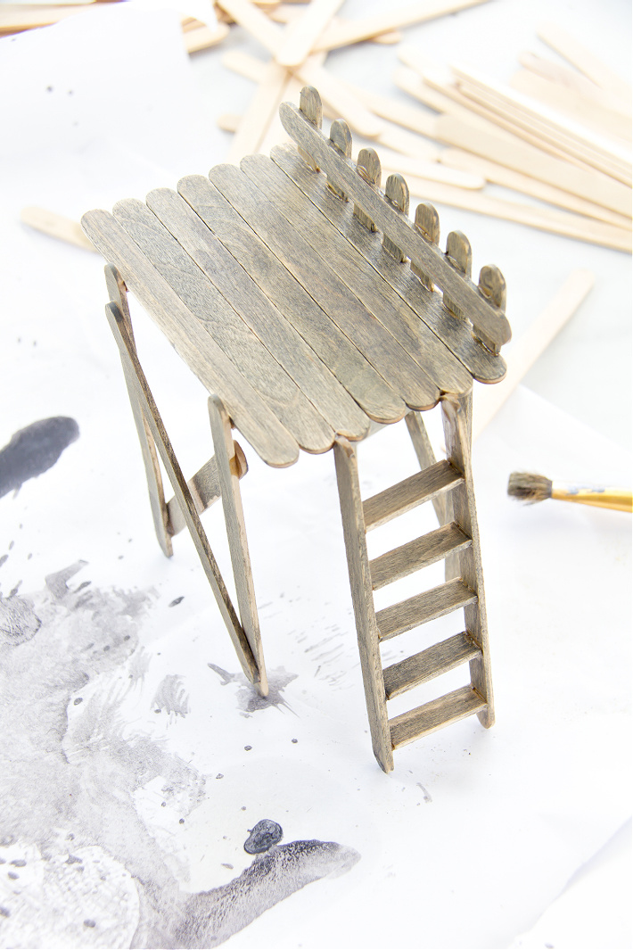 A handmade popsicle stick observation deck for a fairy garden being stained grey.