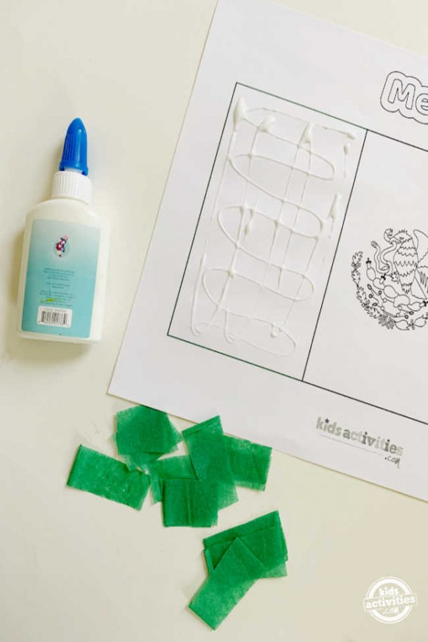 glue smeared to stick the tissue paper square on the free mexican flag printable to make mexican flag activities