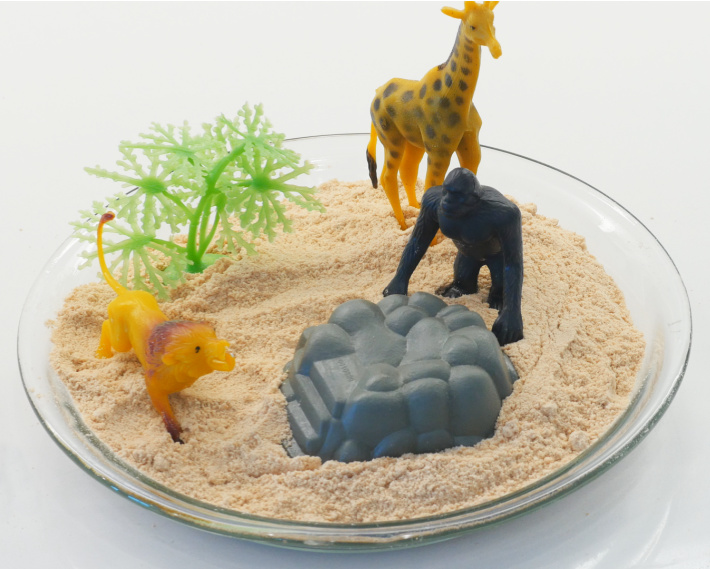 Finished edible sand with sand toys in deep baking dish ready for play