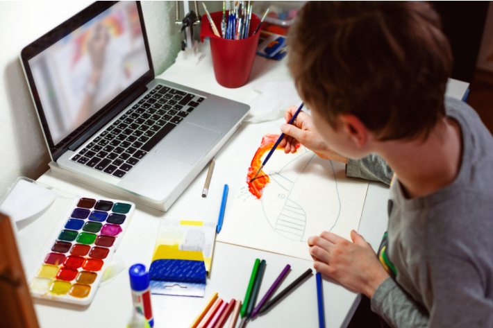 Following along on an art lesson online in the home - Kids Activities Blog - child painting at home while watching online instructor