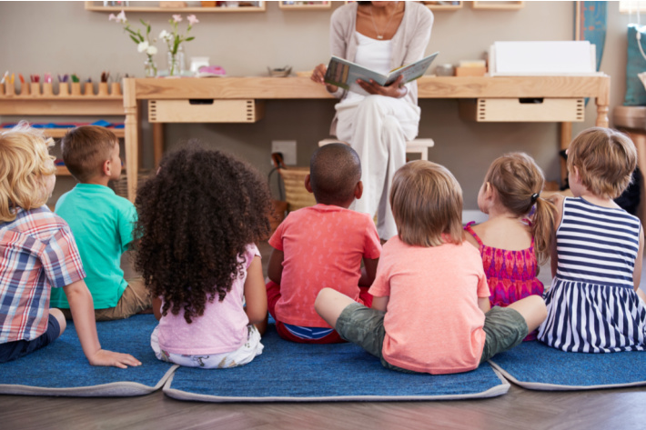 Kindergarten classroom with kids sitting for story time - Kids Activities Blog