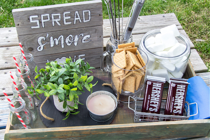 A wood box filled with ingredients to make s'mores including a handmade sign and bottles for drinks.