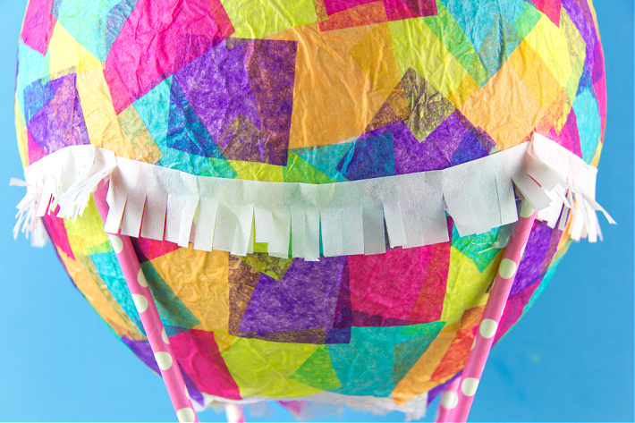 A strip of fringed tissue paper hanging around a tissue paper hot air balloon.