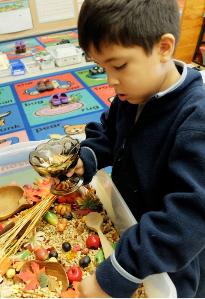 fall sensory bin from Rubber boots and elf shoes - child using autumn sensory bin