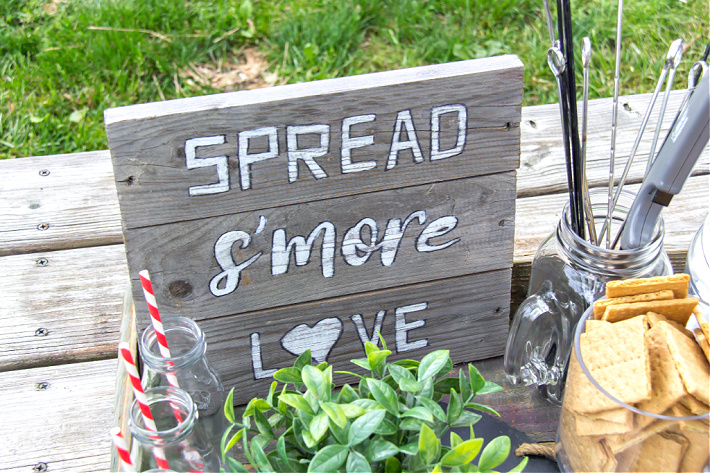 A handmade wood spread s'more love sign on a s'mores tray for a movie night.