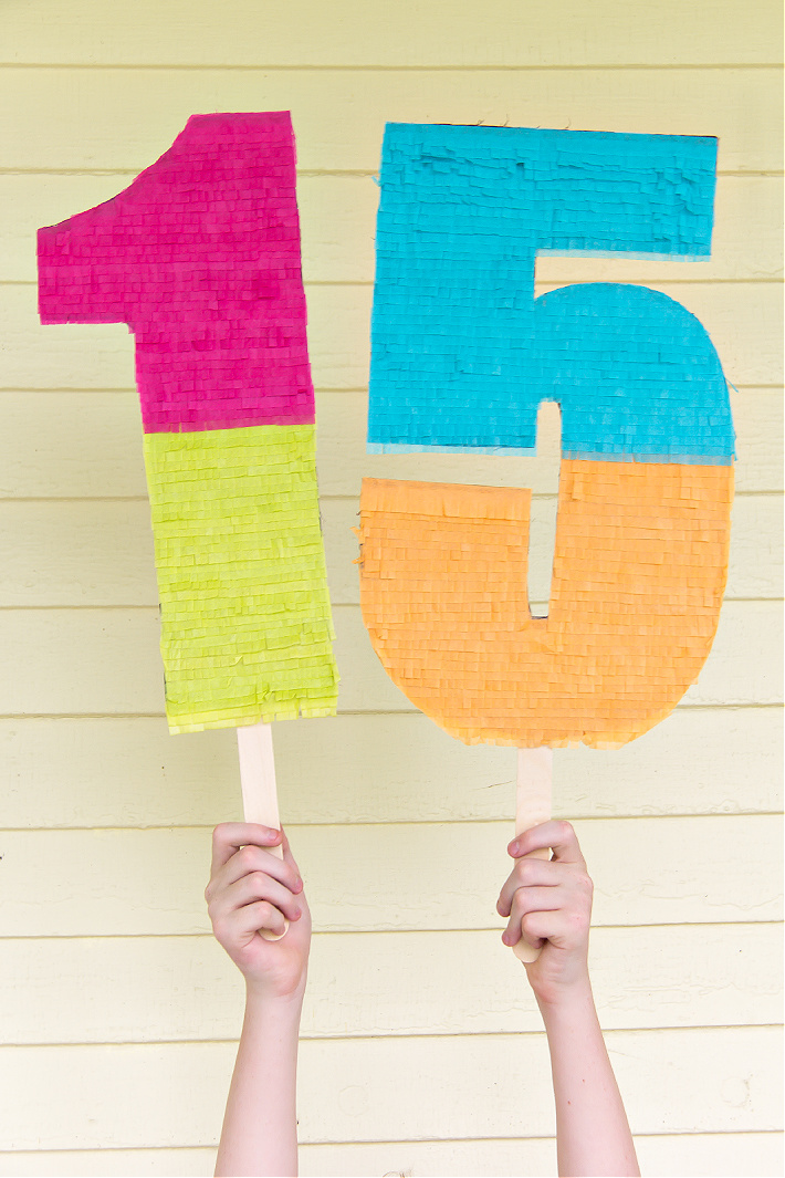 A child's hands holding giant handmade tissue paper birthday celebration numbers.