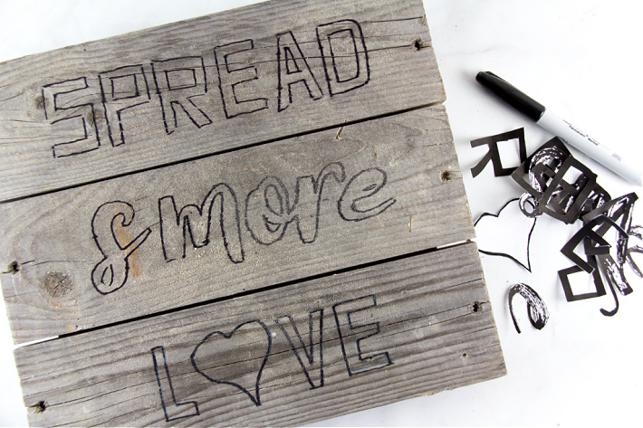 A handmade spread s'more love sign being made with printable letters and paint on wood.
