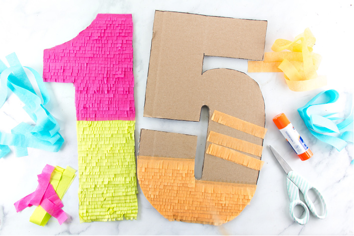 Cardboard numbers with tissue paper fringing on them for a birthday celebration.