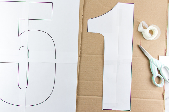 Large paper numbers taped together on top of cardboard boxes to make tissue paper birthday numbers.
