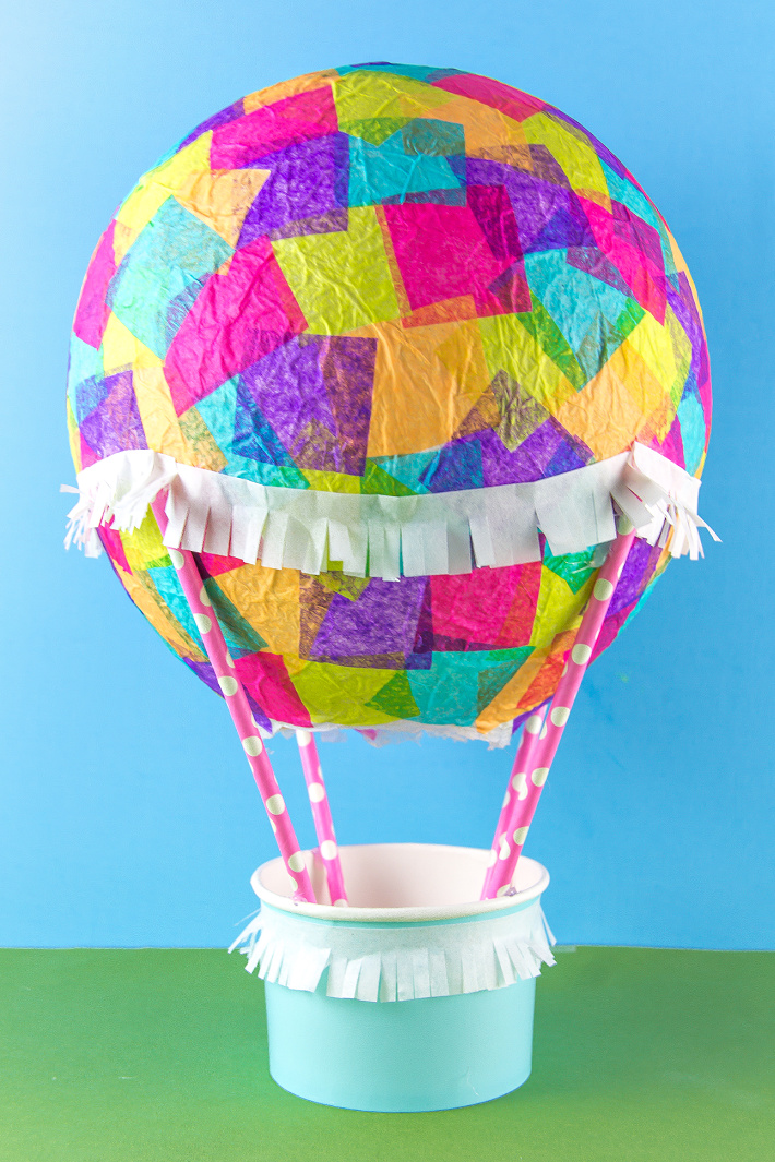 A colorful tissue paper hot air balloon craft with straws and a paper cup.